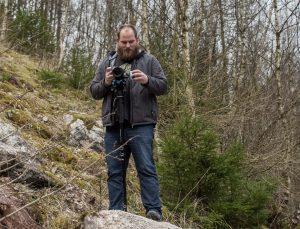 Filmemacher Christian Höke steht eine Kamera haltend auf einem großen Felsen in einem Steinbruch