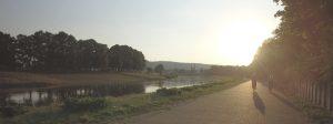 zwei Fahrradfahrer fahren auf einem breiten Radweg entlang. Links von ihnen befindet sich ein Fluss. Sie fahren dem Sonnenuntergang entgegen