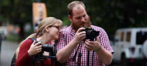 eine Frau und ein Mann halten Kameras fest und schauen auf den Bildschirm einer der Kameras