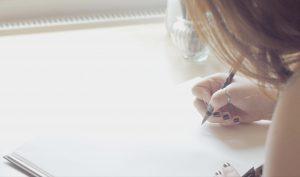 eine junge Frau mit lackierten Fingernägeln zeichnet etwas in ein Skizzenheft