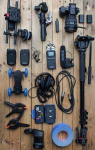 auf einem Tisch liegen Kopfhörer, ein Einbeinstativ, Zoom H5n, XLR Kabel, ein Lavalier