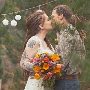 Ein Hochzeitspaar in der Natur mit einem bundten Blumenstrauß