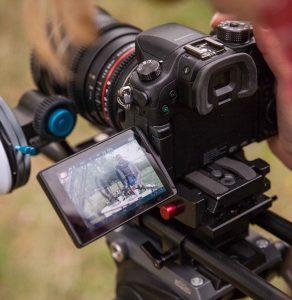 auf dem Display einer DSLR Kamera ist eine junge Frau zu sehen, die im Zuge eines Eventfilm gefilmt wird