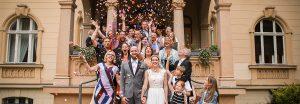 Eine Hochzeitsgesellschaft steht auf einer Treppe und wirft Konfetti in die Luft