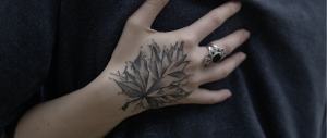 Eine mit einem Blatt tattowirte Hand, an der auch ein Ring ist, fast einem Mann an den Rücken