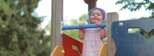 ein kleines lächelndes Mädchen steht auf einem Klettergerüst