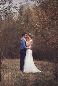 Hochzeitsfilm, ein Hochzeitspaar hat die Arme umeinandergelegt und schaut sich an. Er trägt ein blaues Hemd und Hosenträger und eine blaue Hose. Sie hat ein weißes Hochzeitskleid mit Spitze an und einen bunten Blumenkranz auf dem Kopf. Sie gucken verliebt