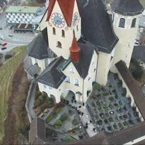 Luftaufnahmen einer Kirche in Österreich während des Auslaufs des Hochzeitspaars